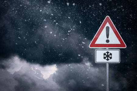 winter tires: Caution - Snow - Warning sign in front of cloudy sky with snowfall.