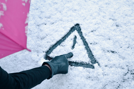 cold weather: Hand Drawn Warning Sign - A woman with umbrella sketches a warning sign drawing in the snow on a car hood. Stock Photo