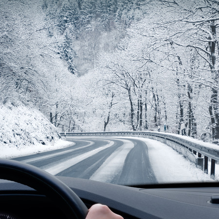 winter road: Winter Driving - Winter country road leading through a mountain landscape. Stock Photo