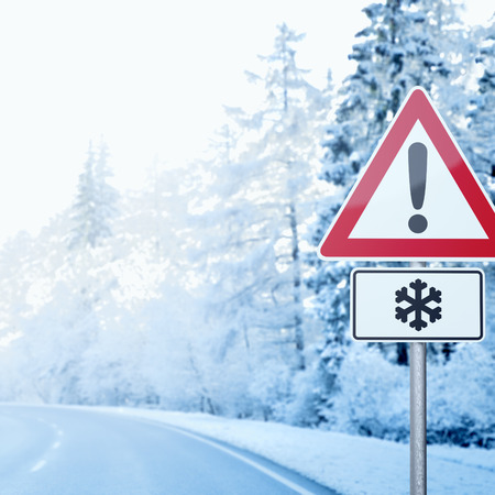 Winter Driving - Curvy winter road with warning sign photo