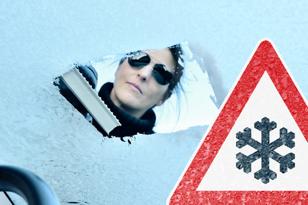 scraping: Winter Driving - Woman with Sunglasses scraping ice from a windshield - Warning Sign