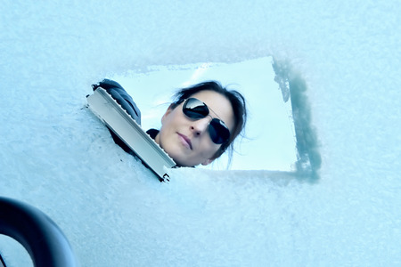 windscreen: Winter Driving - Woman with Sunglasses scraping ice from a windshield