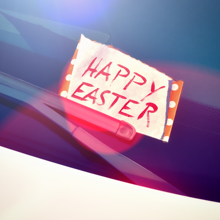 written text: Happy Easter - Message under a windshield wiper with hand written text Stock Photo