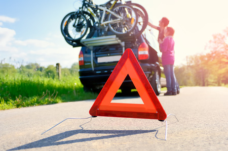 car trouble: Car Trouble on a Holiday trip - Woman is checking the roof box
