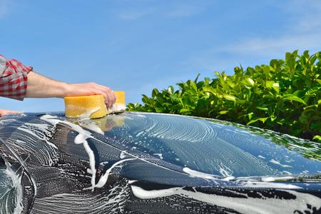 Car Care Man washing a car by hand using a sponge Standard-Bild