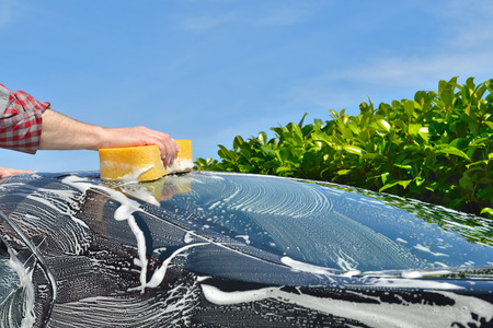 Car Care Man washing a car by hand using a sponge Stock Photo