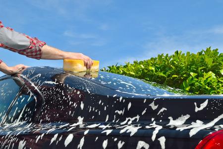 Car Care Man wassen van een auto met de hand met een spons