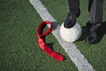 touchline: The Coach Man in business clothing standing on a soccer field one foot on a soccer ball