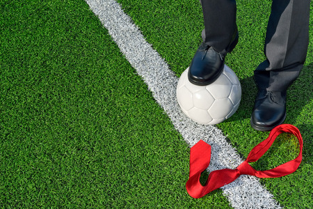 talent management: The Coach Man in business clothing standing on a soccer field one foot on a soccer ball