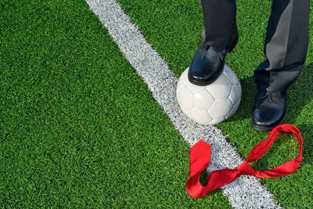 The Coach Man in zakelijke kleding staande op een voetbalveld een voet op een voetbal Stockfoto