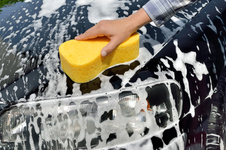 wash car: Car Care Woman washing a car by hand using a sponge Stock Photo
