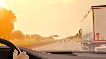 Woon-werkverkeer Het besturen van een auto op de snelweg snelweg bij zonsondergang