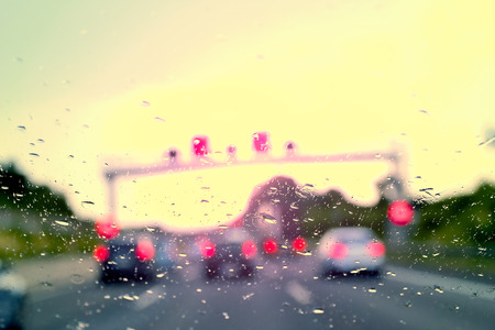 driving conditions: Bad Weather Driving traffic jam on a highway selective focus on raindrops on the windshield