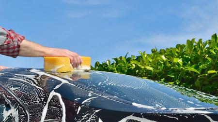 Car Care - Man washing a car by hand using a sponge - copyspace