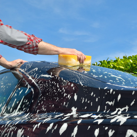car protection: Car Care - Man washing a car by hand using a sponge - copyspace