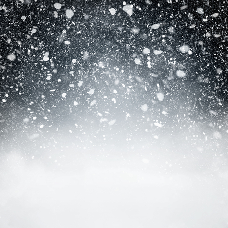ice: Snowfall with Dark Blue Background - Fluffy snowflakes falling in front of a blue background with vignette