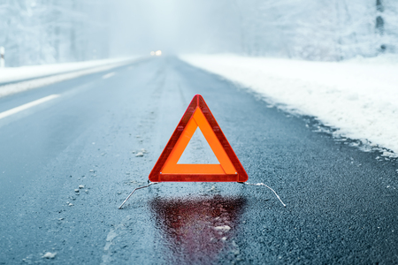 peligro: Winter Driving - Triángulo de advertencia en una carretera de invierno