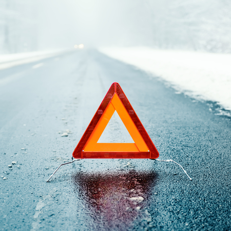 road in winter: Caution - Warning triangle on a winter road Archivio Fotografico