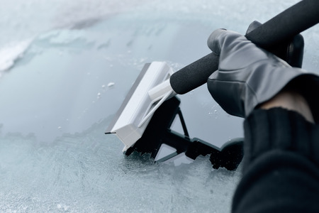 scraping: Winter Driving - Woman scraping ice from a windshield Stock Photo