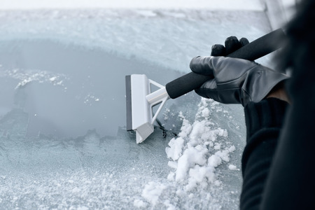 safety gloves: Winter Driving - Woman scraping ice from a windshield Stock Photo