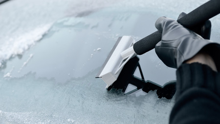Winter Driving - Woman scraping ice from a windshield Stock Photo