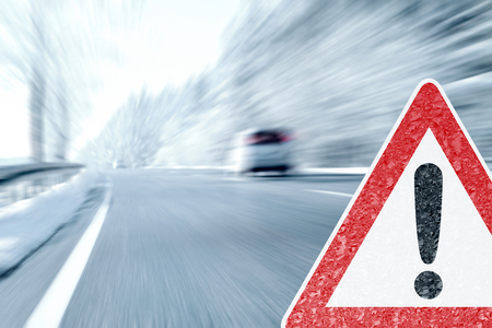 Winter Driving - Icy Road Warning Sign with Stock Photo