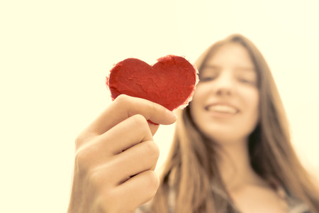 natural looking: Heart Up - Teenage girl holding a heart of paper and having fun - symbol for love - natural looking