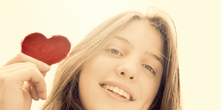 natural looking: Heart Up - Teenage girl holding a heart of paper - symbol for love - natural looking girl Stock Photo