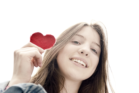 natural looking: Heart up - Teenage girl holding a heart of paper - symbol for love - natural looking girl