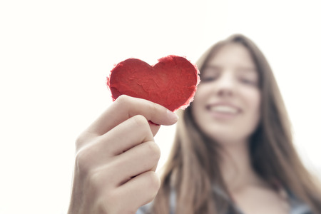 heart hands: Heart up - Teenage girl holding a heart of paper and having fun - symbol for love - natural looking girl