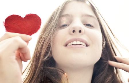 natural looking: Heart Up - Girl holding a heart of paper - symbol for love - natural looking