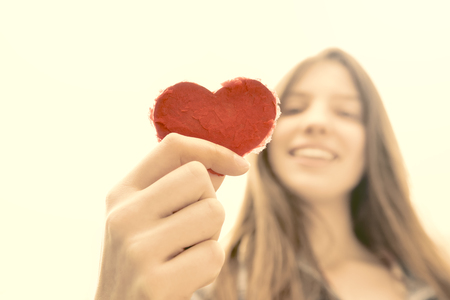 natural looking: Heart up - Teenage girl holding a heart of paper and having fun - symbol for love - natural looking girl