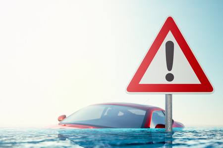 Warning sign standing in flood water in front of a flooded car