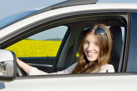 Teen Drivers - Happy teenage vrouwelijke chauffeur zitten in haar auto Alle die staat in de voorkant van een canolagebied