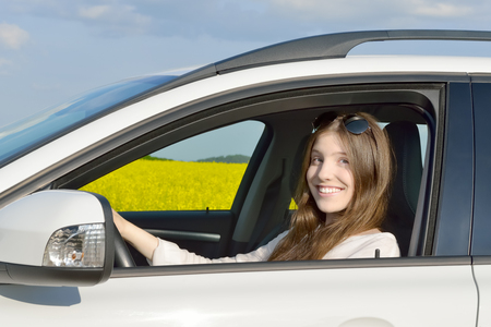 Teen Drivers - Happy teenage female driver sitting in her car All which is standing in front of a canola field