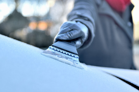 Winter Driving - Woman is scraping ice from the frozen windows of her car Stok Fotoğraf