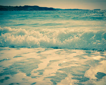 Waves breaking on a sandy beach on the shore of the mediterranean coast. Vintage stylized photo.