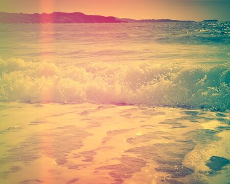 Waves breaking on a sandy beach on the shore of the mediterranean coast. Vintage stylized photo with light leaks in beautiful and vivid colors. Stok Fotoğraf