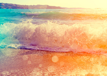 Waves breaking on a beautiful sandy beach on the shore of the mediterranean coast. Vintage stylized photo with light leaks and bokeh effect. Stok Fotoğraf