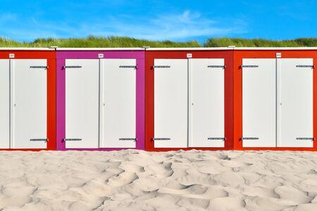 On the Beach by the Sea - beautiful colorful beach huts on a sandy beach on a sunny day Stok Fotoğraf