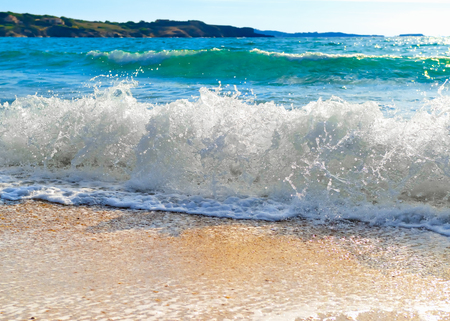 On the Beach by the Sea - waves breaking on a sandy beach on the shore of the mediterranean coast
