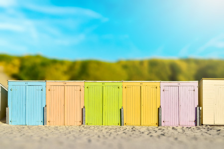 On the beach by the sea - beautiful colorful beach huts on a sandy beach on a sunny day - miniature effect - vintage style Stok Fotoğraf