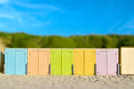 On the beach by the sea - beautiful colorful beach huts on a sandy beach on a sunny day - miniature effect Stok Fotoğraf