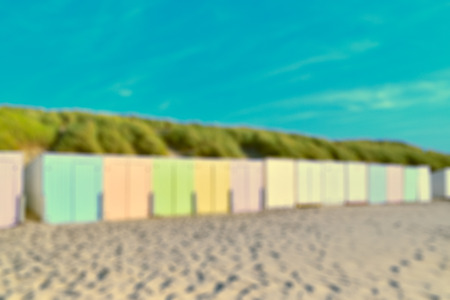 On the beach by the sea - beautiful colorful beach huts on a sandy beach on a beautiful day - defocused - vintage style