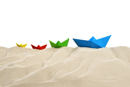 On the beach - sand dune with four colorful paper boats in front of a white background - clipping path included Stok Fotoğraf