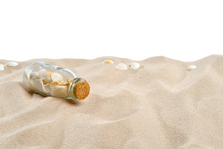 On the beach - sand dune with bottle and shells in front of a white background - clipping path included