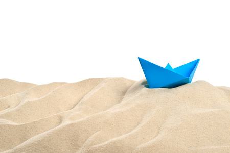 On the beach - sand dune with blue paper boat in front of a white background - clipping path included