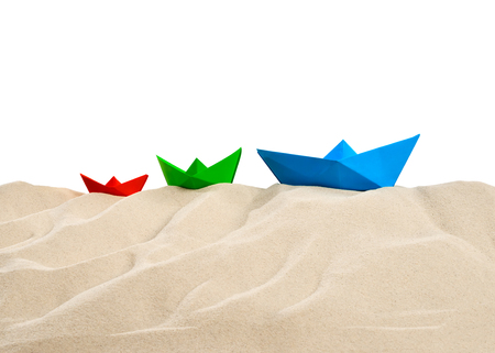 On the beach - sand dune with three colorful paper boats in front of a white background - clipping path included Stok Fotoğraf