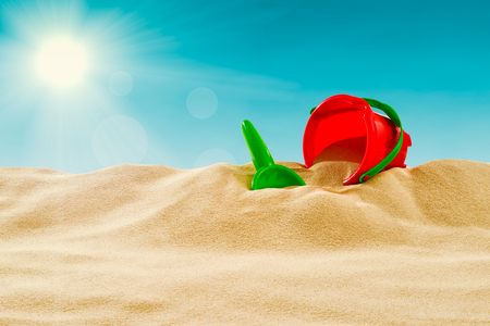 On the Beach - Sand dune with sand toys on a sunny day; Vintage stylized