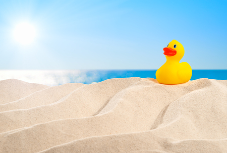 On the beach - rubber duck on a sand dune in front of beautiful azure sea